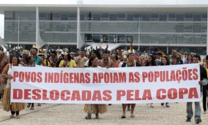 Different indigenous ethnic groups carry a banner during a protest against the Indian policy of President Dilma Rousseff's government and the costs of the 2014 World Cup in front of the Planalto Palace in Brasilia